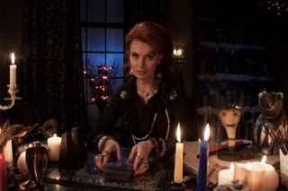 immagine che ritrae un'operatrice esoterica in una stanza illuminata da camdela che tiene tra le mani un mazzo di carte