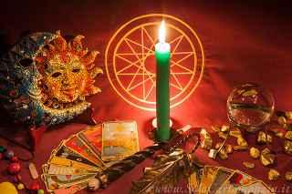 immagine che ritrae una candela verde accesa su un tavolo con materiale da divinazione