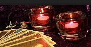 immagine che ritrae due candele rosse accese e alcune carte