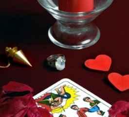 immagine che ritrae una carta dei tarocchi su panno rosso con dei piccoli cuori un pendolino e una candela