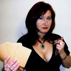 immagine che ritrae un operatrice esotercia che tiene un mazzo di carte nella mano destra