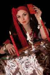 immagine che ritrae una cartomante con un fazzoletto rosso in testa che lancia una carta