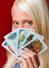 immagine che ritrae una cartomante che tiene sul viso cinque carte degli arcani