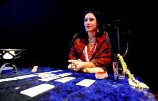 immagine che ritrae una cartomante seduta al tavolo di divinazione