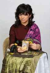 immagine che ritrae un'operatrice esoterica vestita di viola che tiene una carta in mano