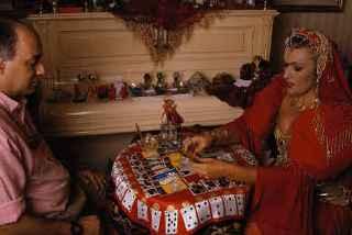 immagine che ritrae un'operatrice esoterica vestita di rosso che legge le carte al consultante seduto di fronte a lei
