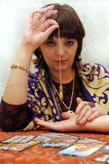 immagine che ritrae una cartomante che consulta il pendolo